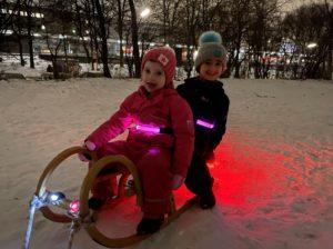 Kinder auf Schlitten mit Beleuchtung