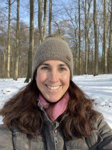 Frau mit Mütze im Winterwald