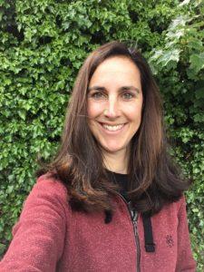 Frau mit langen braunen Haaren vor grüner Hecke