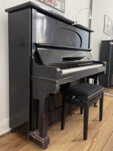dunkles Klavier mit Klavierhocker