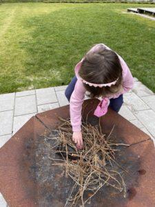 Kind holt ein Ei aus der Feuerschale