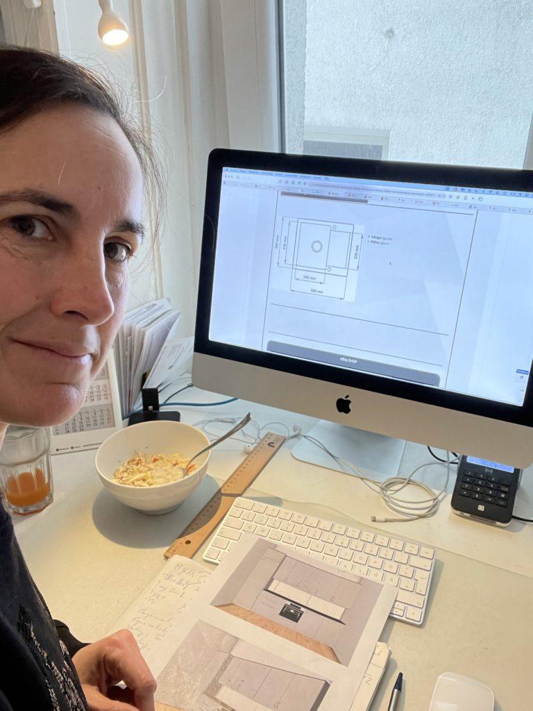 Frau mit Frühstück vor dem Computer