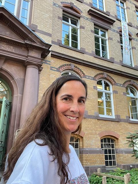Frau vor Schulgebäude